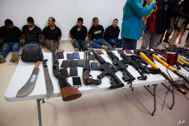 Suspects in the assassination of Haiti's President Jovenel Moise are shown to the media, along with the weapons and equipment…