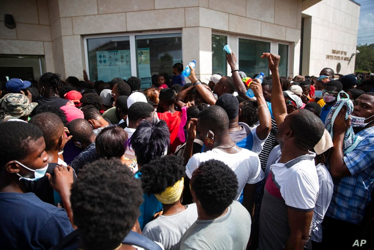 Haitians gather in front of the U.S. Embassy amid rumors on radio and social media that the U.S. will be handing out exile and...