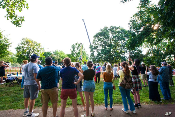 Onlookers watch as the monument of Confederate General Robert E. Lee is lifted from its pedestal on Saturday, July 10, 2021 in…