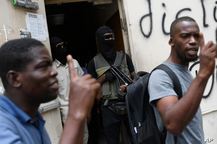 The bodyguards of current and former senators being questioned by prosecutors wait in the doorway outside the court, behind men who support the politicians in Port-au-Prince, Haiti, July 12, 2021.