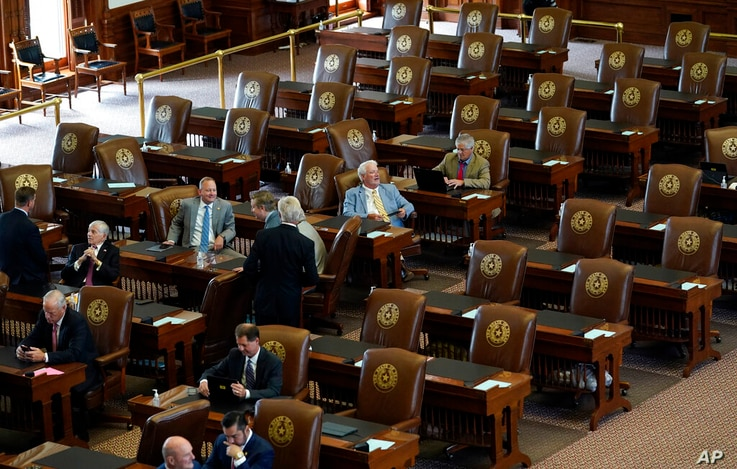 Empty seats are seen in the House Chamber at the Texas Capitol, Tuesday, July 13, 2021, in Austin, Texas. Texas Democrats left…