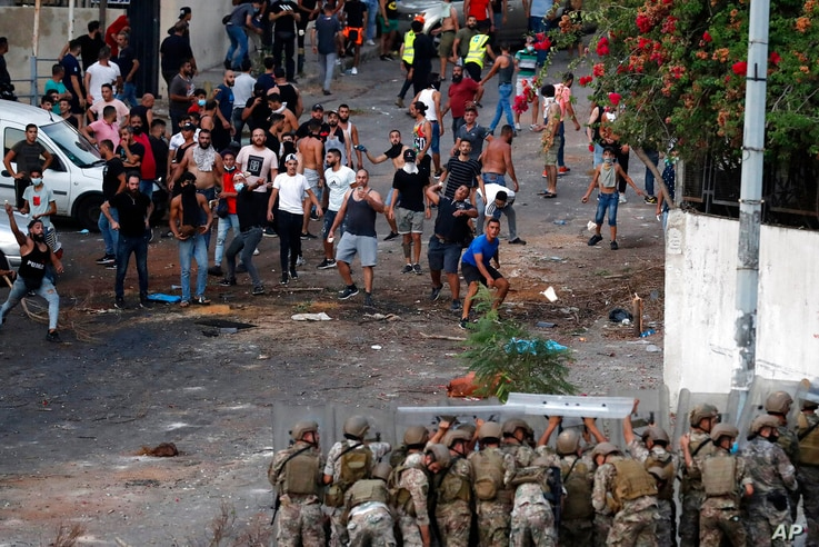 """Lebanese soldiers hide from stones behind their protective shield as they clash with supporters of Prime Minister-designate Saad Hariri who stepped down on Thursday in Beirut, Lebanon, Thursday, July 15, 2021. Hariri says he is stepping down, nine months after he was named to the post by the parliament. He is citing """"key differences"""" with the country's president, Michel Aoun. (AP Photo/Hussein Malla)"""