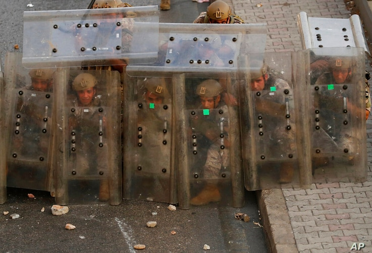 Lebanese soldiers hide from stones behind their protective shields as they clash with supporters of Prime Minister-designate…