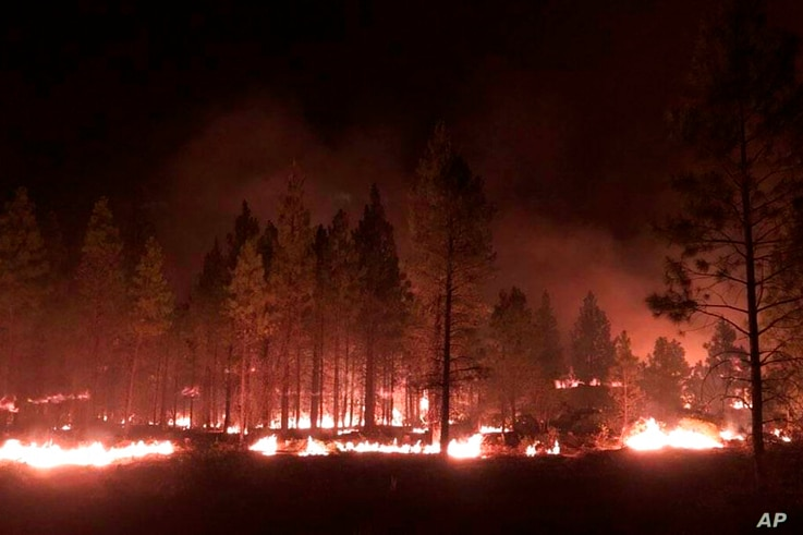 In this photo provided by the Bootleg Fire Incident Command, the Bootleg Fire burns at night near Highway 34 in southern Oregon…