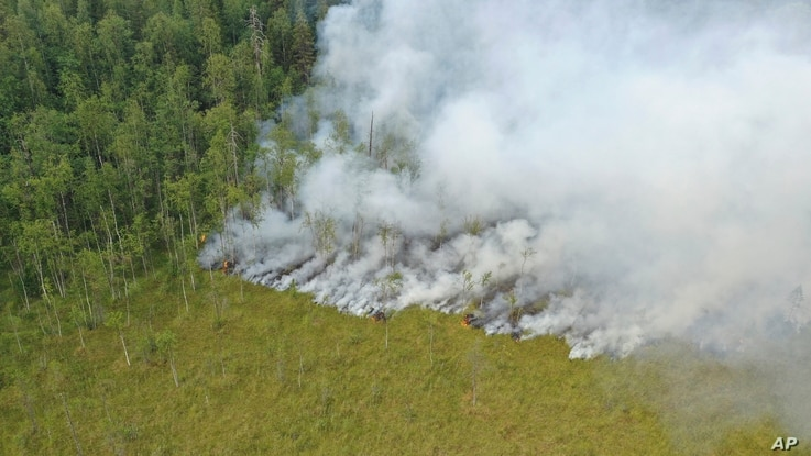 An aerial view of a forest fire in Pryazhinsky District of the Republic of Karelia, about 700 km.(438 miles) south-west of Moscow, Russia on Wednesday, July 21, 2021. Thousands of wildfires engulf broad expanses of Russia each year, destroying forests and shrouding regions in acrid smoke. (AP Photo/Ilya Timin)