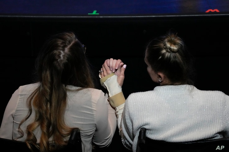Angela Gonzalez, right, holds hands with her daughter Deven, as both sit in wheelchairs due to their injuries during the…