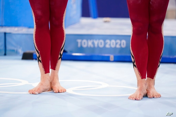 German gymnasts stand with their unitard costumes and wait to perform during the women's artistic gymnastic qualifications at...