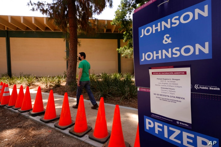 FILE - Carlos Arrendondo arrives for his appointment to get vaccinated, as banners advertise the availability of the Johnson &…