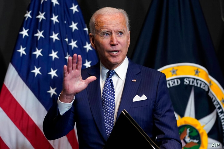 President Joe Biden finishes leaves after speaking during a visits to the Office of the Director of National Intelligence in...