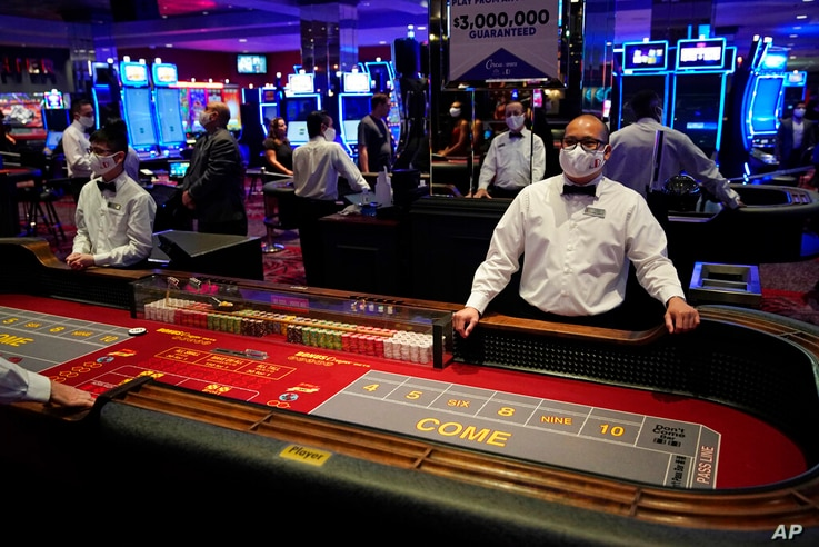 FILE - Dealers in masks wait for customers before the reopening of the D Las Vegas hotel and casino in Las Vegas, in this...