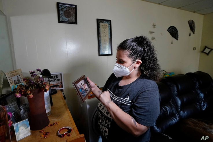 Roxanne Schaefer holds a photograph in the living room of her apartment, in West Warwick, R.I., Tuesday, July 27, 2021…
