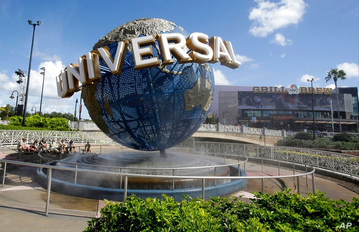 FILE-In this Thursday, Oct. 22, 2015 file photo, park guests relax and cool off with a water mist under the globe at Universal...