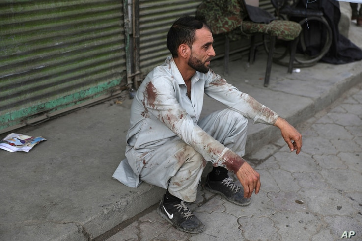 A blood-stained man rests after he helped people who were injured in a deadly bomb explosion in Kabul, Afghanistan, July 13, 2021.