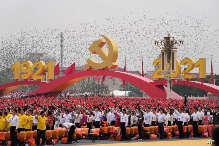 Attendees wave Chinese flags during a ceremony at Tiananmen Square to mark the 100th anniversary of the founding of the ruling Chinese Communist Party in Beijing.