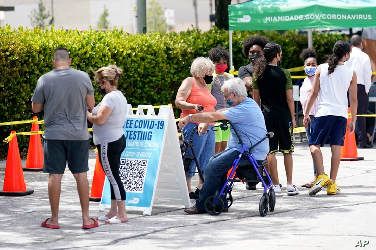 People wait in line at a Miami-Dade County COVID-19 testing site, July 26, 2021, in Hialeah, Florida.