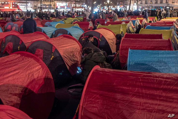FILE - Migrants set up tents on the Republic square to draw attention to their living conditions and to demand accommodation, in Paris, France, March 25, 2021.