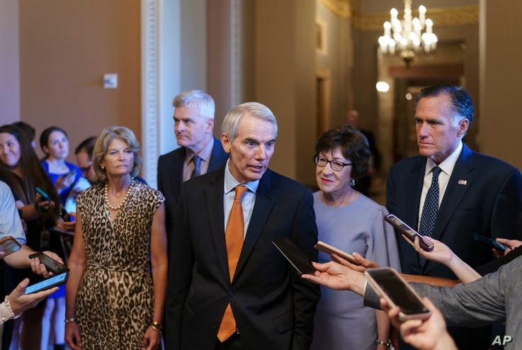 Republican Senators Rob Portman, center, joined by, from left, Lisa Murkowski, Bill Cassidy, Susan Collins, and Mitt Romney, announces an agreement with Democrats on a $1 trillion infrastructure bill, at the Capitol in Washington, July 28, 2021.