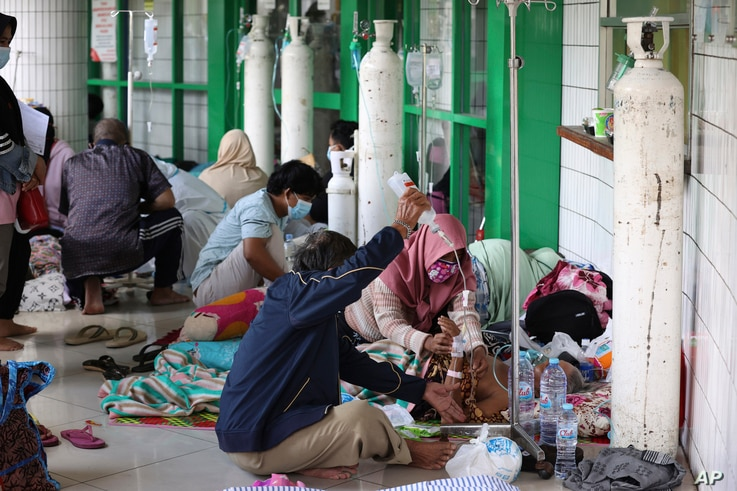Oxygen tanks are prepared for patients in the hallway of an overcrowded hospital amid a surge of COVID-19 cases, in Surabaya, East Java, Indonesia, July 9, 2021.