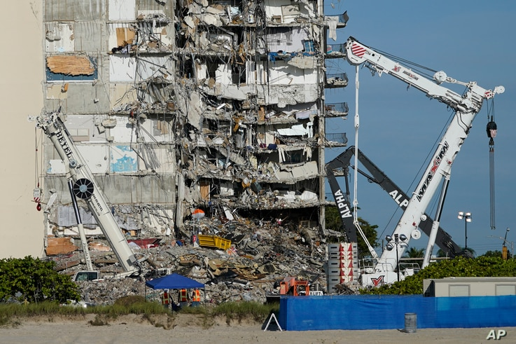 Workers peer up at the rubble pile at the partially collapsed Champlain Towers South condo building, ahead of a visit to the site by President Joe Biden, in Surfside, Florida, July 1, 2021.