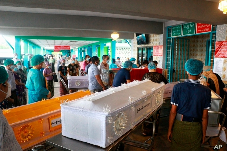 People wearing face masks wait while caskets with bodies are queued outside a crematorium at the Yay Way cemetery in Yangon, Myanmar, July 14, 2021.