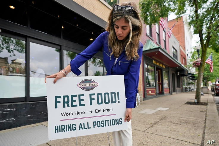 Coleen Piteo, director of marketing at Yours Truly restaurant, puts out a sign for hiring, June 3, 2021, in Chagrin Falls, Ohio.