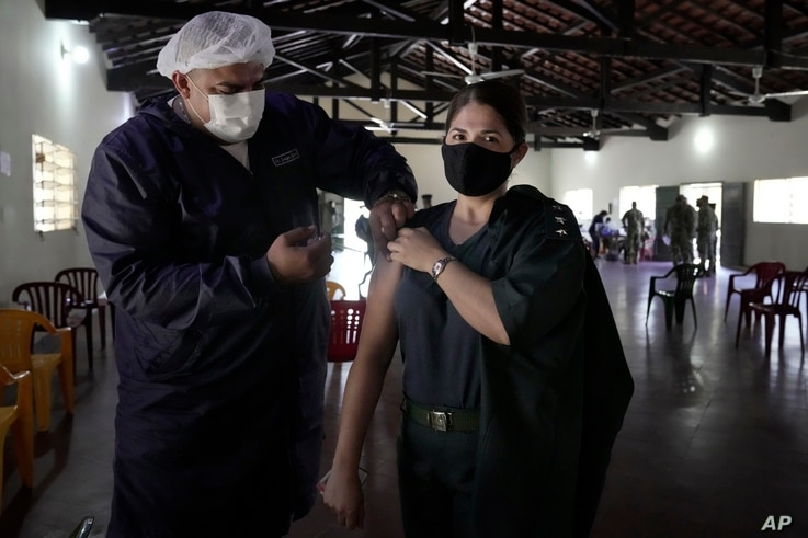 Captain Jackeline Guillen gets a shot of the Pfizer COVID-19 vaccine from an Health Ministry worker at a military barracks in Mariano Roque Alonso, Paraguay, July 12, 2021.