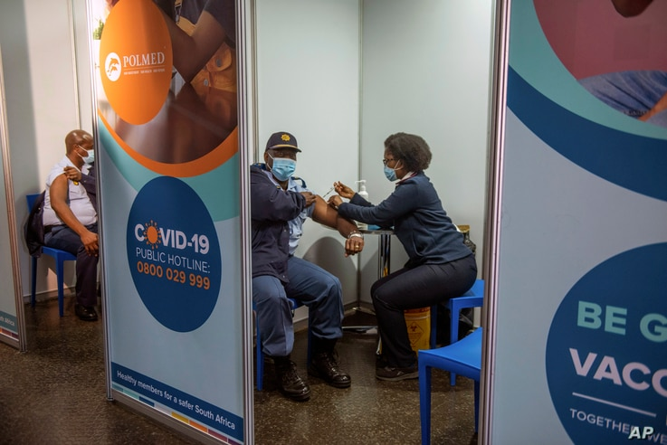 FILE - A policeman receives his COVID-19 vaccine in Soweto, South Africa, July 5 2021.