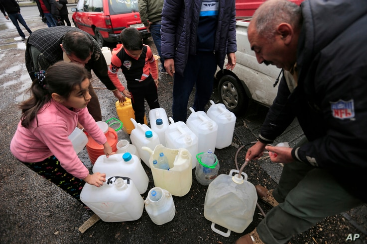 FILE — People fill plastic containers with water from a tap in Damascus, Syria, Jan. 16, 2017.