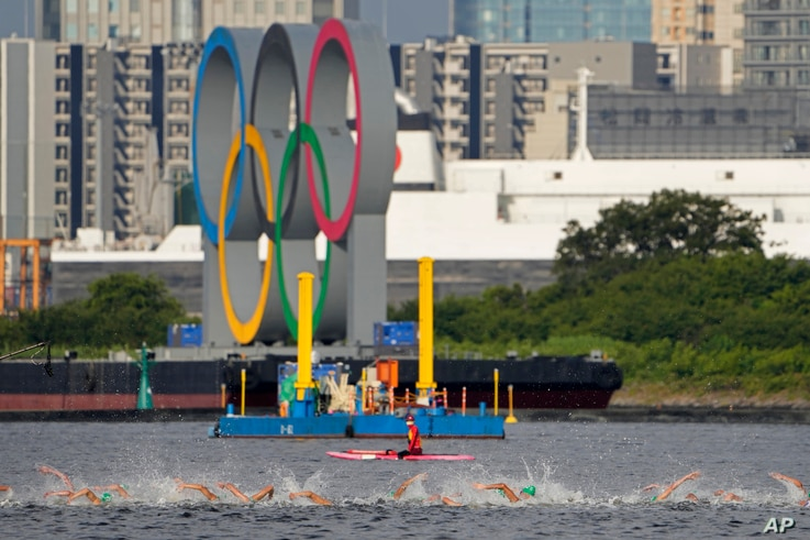 Athletes compete in the swim leg of the men's individual triathlon at the 2020 Summer Olympics, in Tokyo, Japan, July 26, 2021.