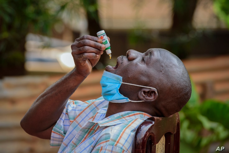 A man with a cough but who had not been tested for the coronavirus uses COVIDEX, a locally-made herbal medicine approved by the government for use as a supportive treatment for viral infections, in Kampala, Uganda, July 6, 2021.