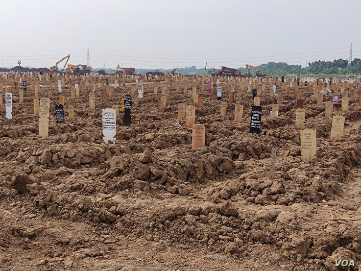 Makeshift grave markers are seen at a cemetery for COVID-19 victims in TPU Rorotan, north Jakarta, Indonesia, July 8, 2021. The 8,000 square meter plot of land, which saw its first funerals in late March, is now almost full. (Indra Yoga/VOA Indonesian)