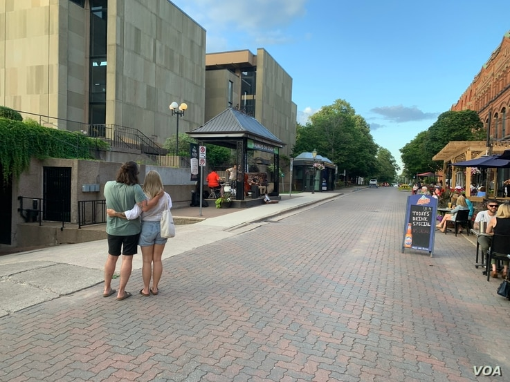 A Charlottetown street is of interest to a couple looking at the crowded bar patios. (Jay Heisler/VOA)