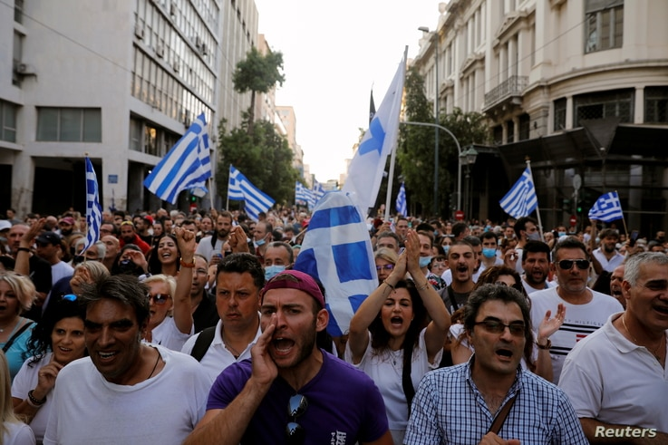 Demonstrators shout slogans during a protest against COVID-19 vaccinations, in Athens, Greece, July 24, 2021.