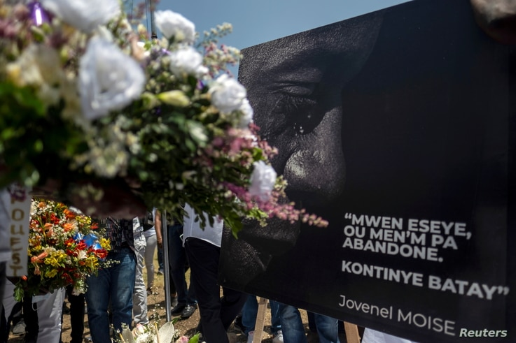 """People place a portrait of slain Haitian President Jovenel Moise with a quote from him that reads in Creole """"I try, you don't give up. Continue fighting,"""" at a memorial outside the Presidential Palace, in Port-au-Prince, Haiti, July 14, 2021."""