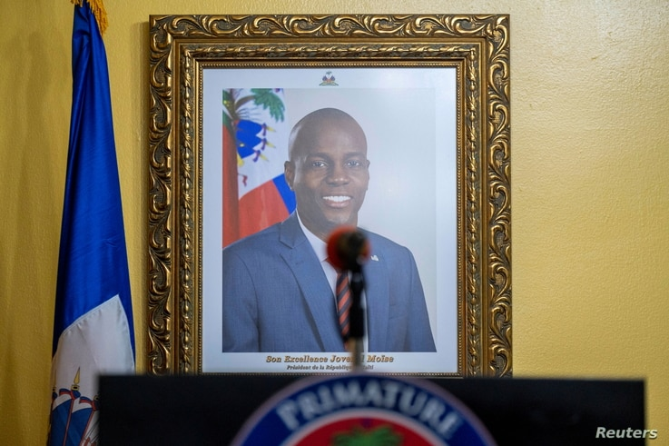 A picture of the late Haitian President Jovenel Moise hangs on a wall before a news conference by interim Prime Minister Claude Joseph, in Port-au-Prince, Haiti, July 13, 2021.