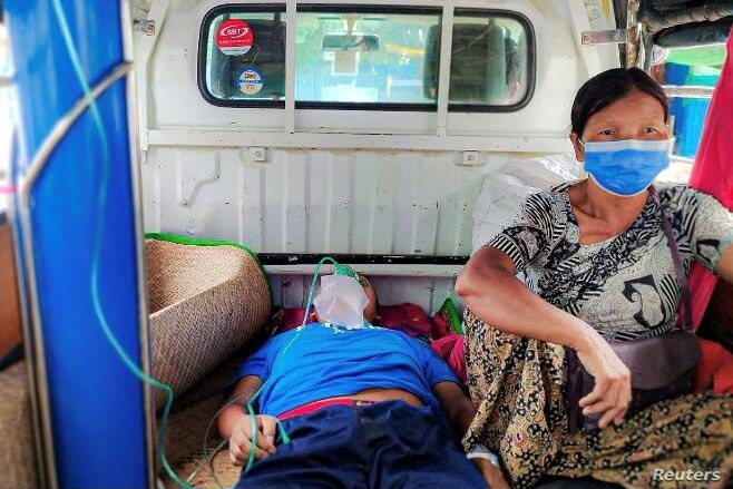 FILE - A relative sits with a COVID-19 patient being taken to hospital in the town of Kale, Sagaing region, Myanmar, July 6, 2021.