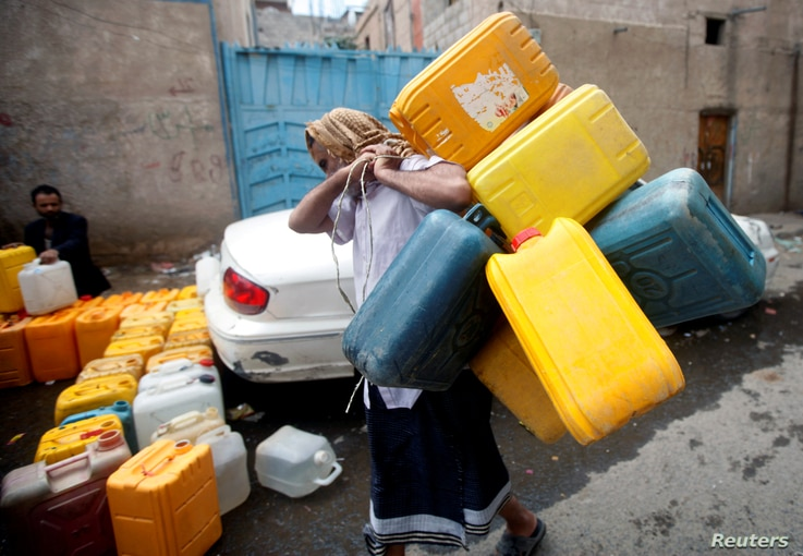 FILE — A man carries jerry cans to fill them with water from a charity tap amid a shortage of drinking water in Sanaa, Yemen, Oct. 11, 2019.