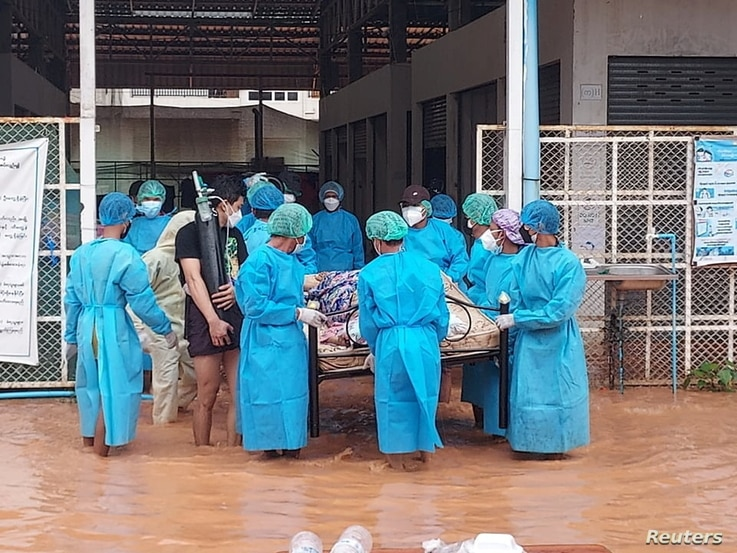 Volunteers in protective suits carry a COVID-19 patient lying on a hospital bed as they try to relocate patients from the COVID-19 center due to the flood in Myawaddy, Karen state, Myanmar, July 26, 2021.