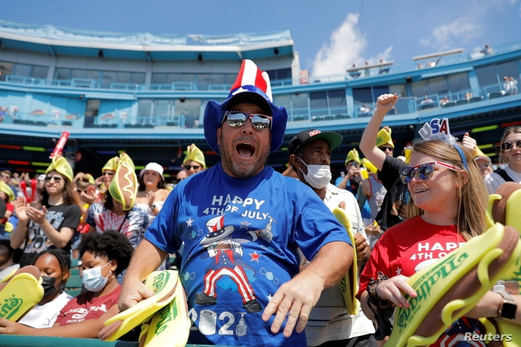 People celebrate Independence Day at the Nathan's Famous Fourth of July Hot Dog-Eating Contest held at Maimonides Park in Brooklyn, New York City, July 4, 2021.