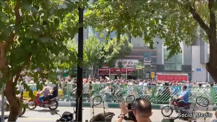 In this screen grab of a video shared on social media, Iranians march and chant antigovernment slogans on a street in central Tehran, July 26, 2021.