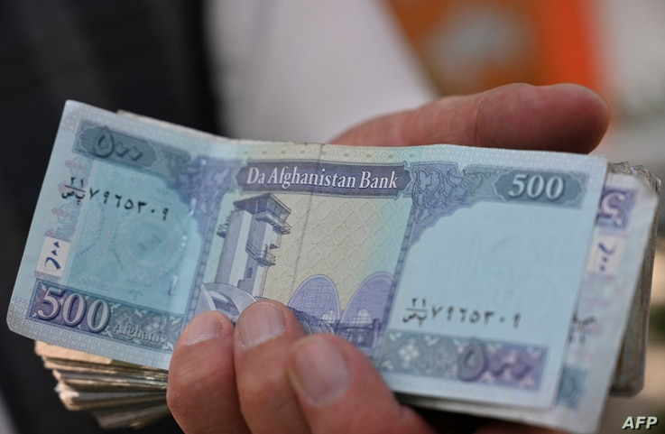 A money changer holds Afghan Afghan banknotes on a street in Kabul on June 30, 2021 (Photo ADEK BERRY / AFP)