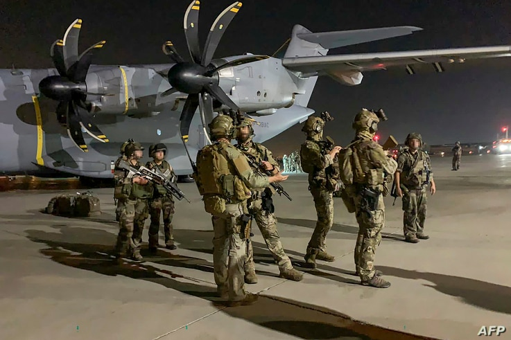 French Special Forces Soldiers stand guard near a military plane at airport in Kabul on August 17, 2021, as they arrive to…