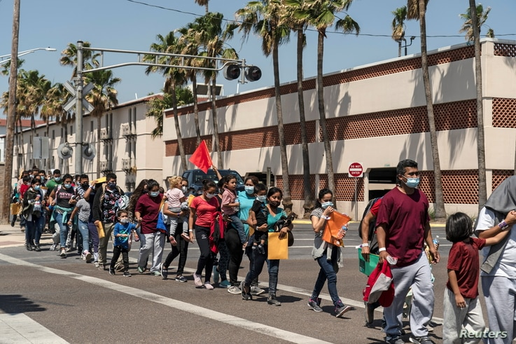 Asylum-seeking migrants' families walk to a temporary shelter run by a local charity organization after undergoing tests for...