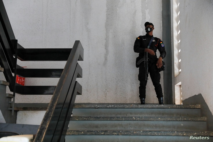 A police officer stands guard before the bail hearing of the twenty-one  people who where detained by police and accused of…