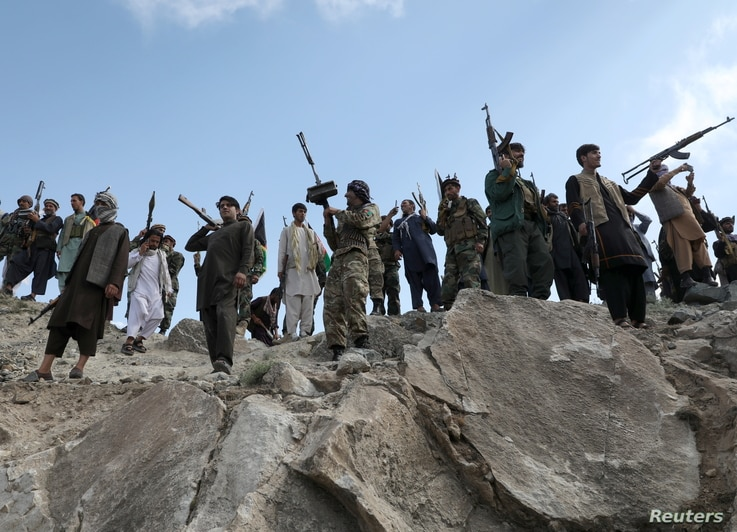 Armed men attend a gathering to announce their support for Afghan security forces and that they are ready to fight against the...