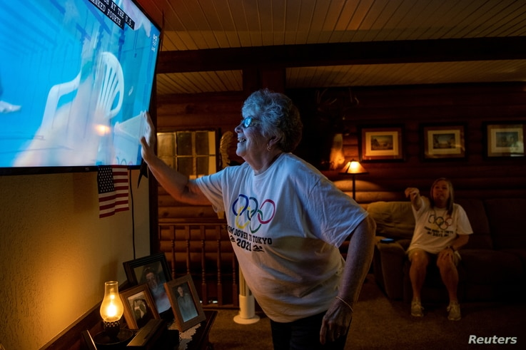 Karen Armstrong reaches to touch displayed on a screen shoulder of her grandson, U.S. swimmer Hunter Armstrong, before he makes...