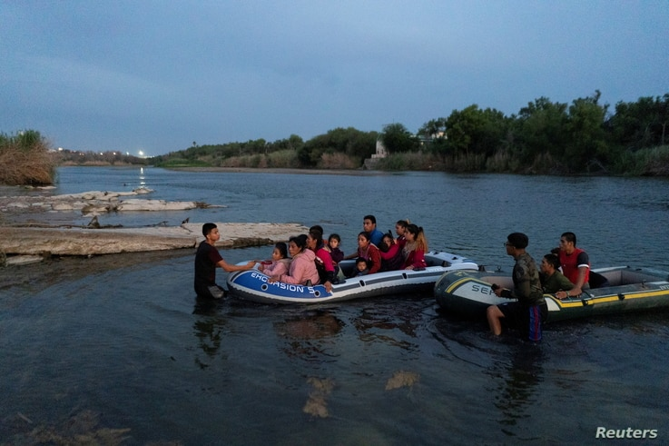 FILE PHOTO: Asylum-seeking migrant families from Guatemala and Honduras arrive to the U.S. side of the bank on an inflatable...
