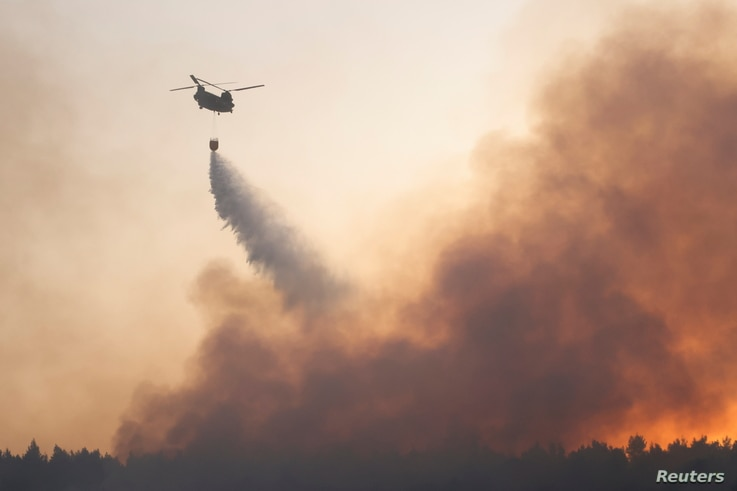 A chinook helicopter makes a water drop as a wildfire continues to rage in Varympompi suburb, north of Athens, Greece, August 4…
