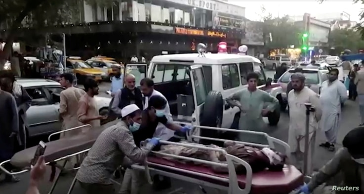 A screen grab shows people carrying an injured person to a hospital after an attack at Kabul airport, in Kabul, Afghanistan August 26, 2021. REUTERS TV/1TV/Handout via REUTERS THIS IMAGE HAS BEEN SUPPLIED BY A THIRD PARTY. MANDATORY CREDIT. NO RESALES. NO ARCHIVES. AFGHANISTAN OUT. NO COMMERCIAL OR EDITORIAL SALES IN AFGHANISTAN