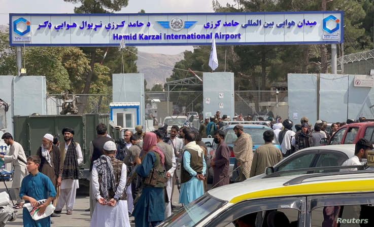 People gather at the entrance gate of Hamid Karzai International Airport a day after U.S troops withdrawal, in Kabul,…